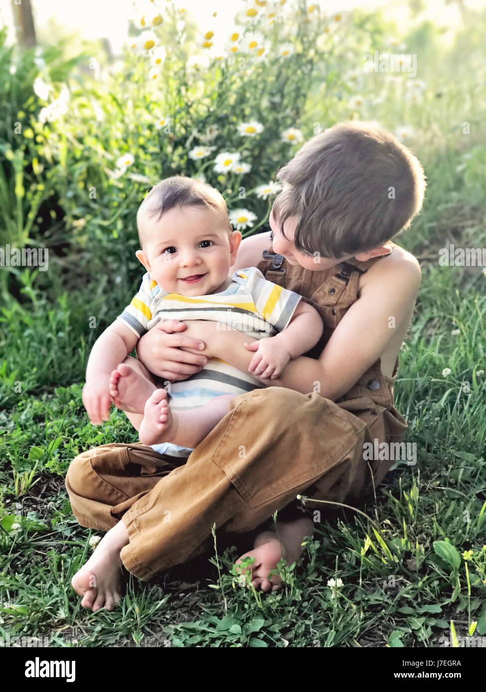 child holding baby - Stock Image