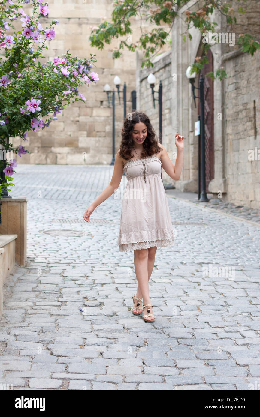 Full length portrait of curly young girl wearing biege romantic dress strolling through old streets of Inner City - Stock Image