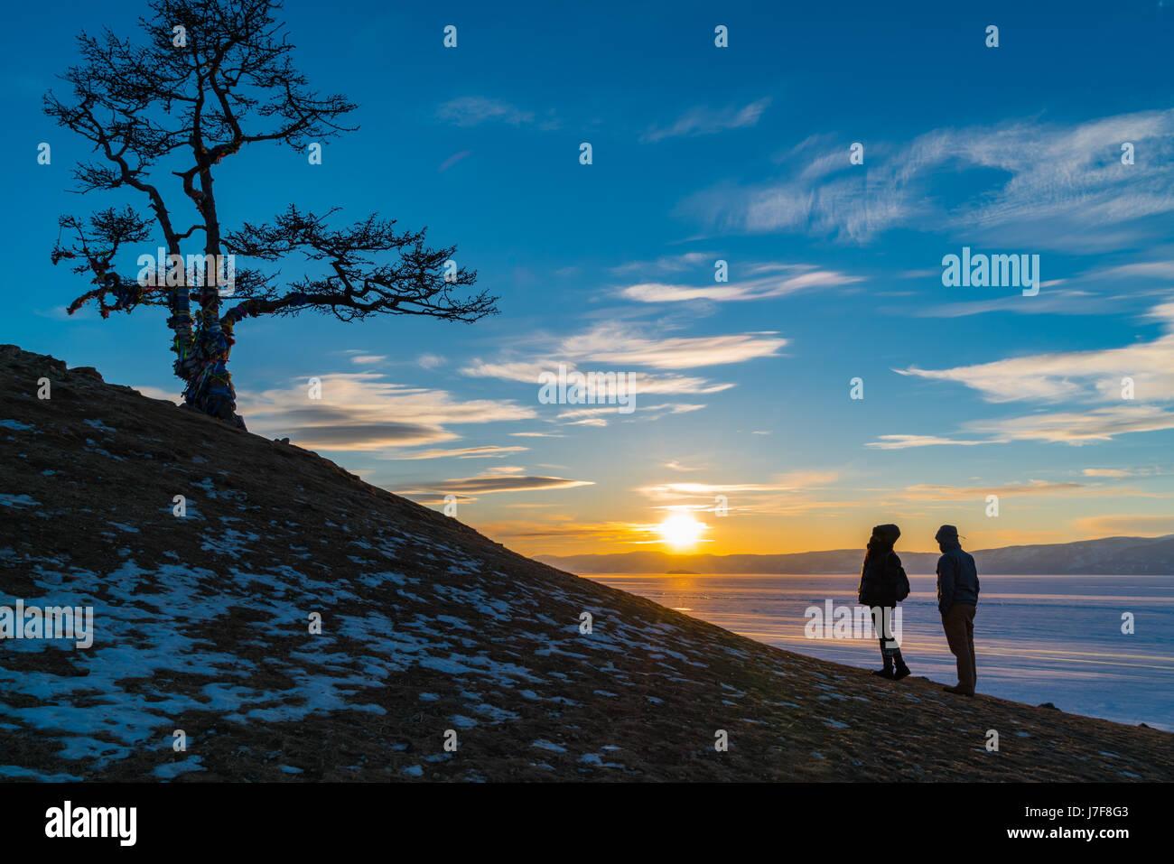 Silhouette scene of sacred tree at Cape Burkhan on Olkhon Island in Lake Baikal at sunset - Stock Image