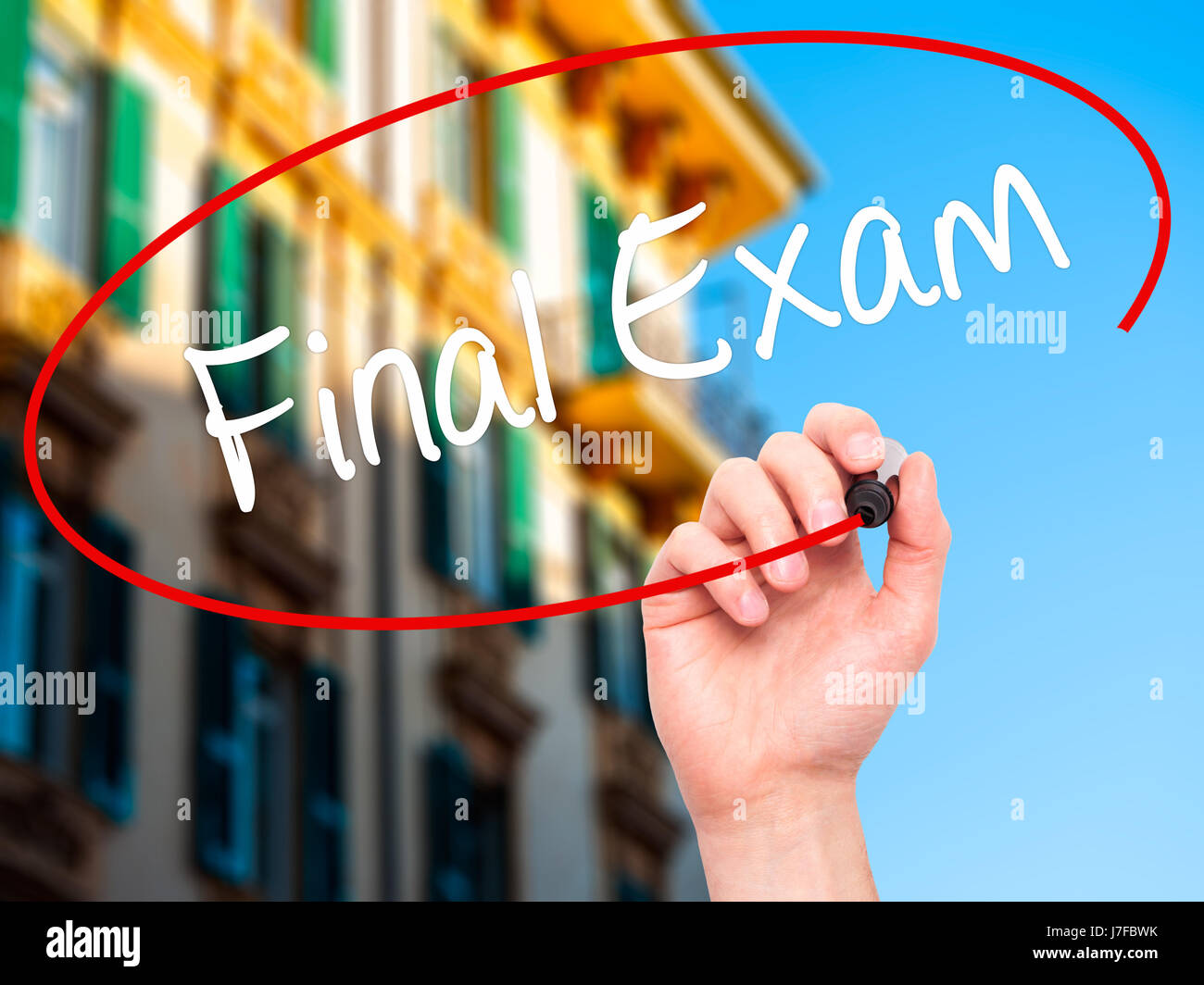 Man Hand writing Final Exam with black marker on visual screen Stock
