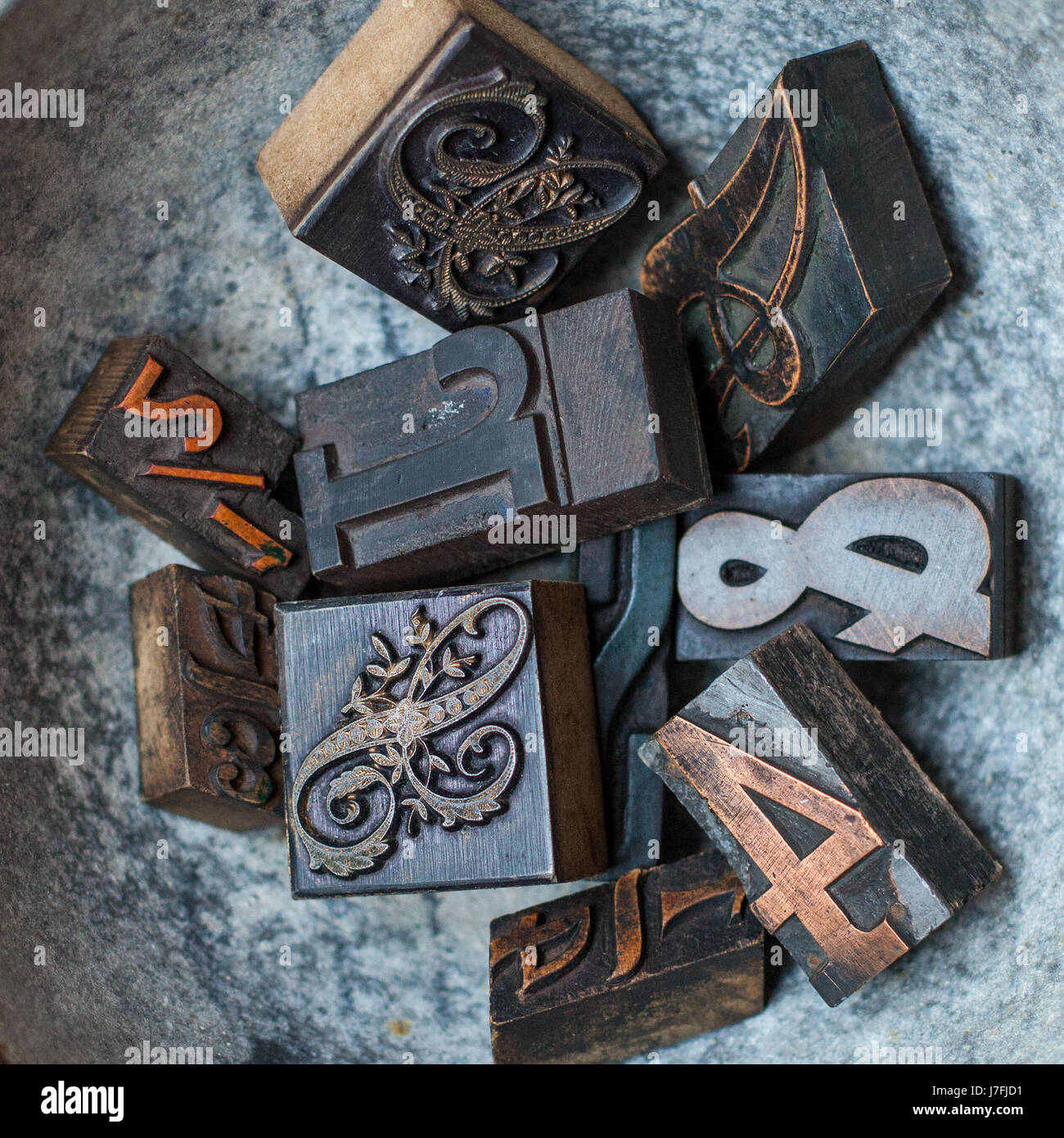 Old wooden letterpress block type of different fonts in a rustic bowl. Letters for printing. Bold letter press blocks. - Stock Image