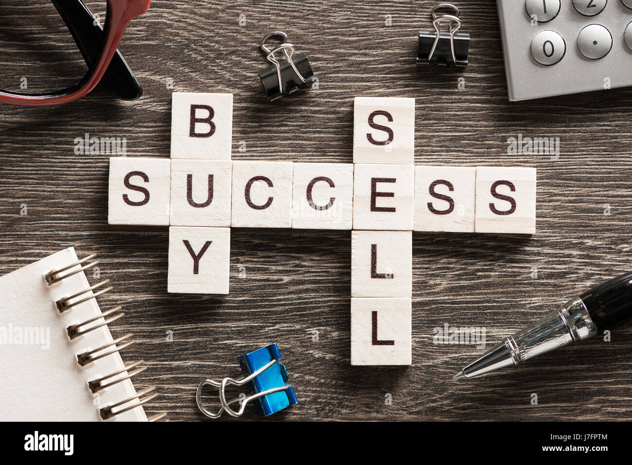 Buy sell success concepts collected in crossword on wooden table - Stock Image