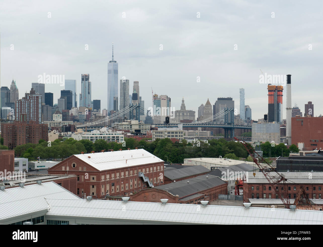 The Brooklyn Navy Yard in the foreground with the Lower Manhattan skyline behind it. The 300-acre Navy Yard had Stock Photo
