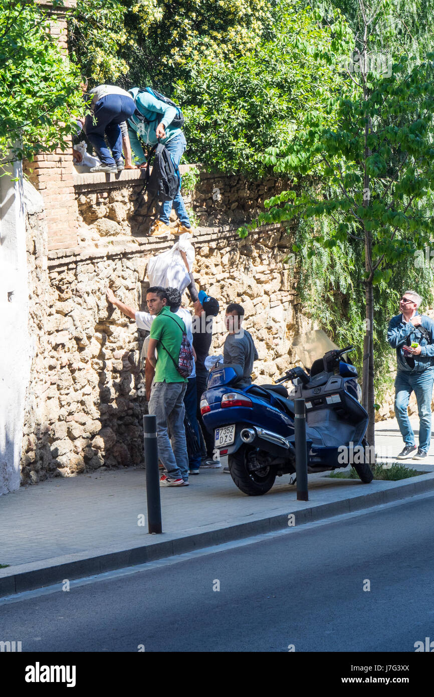 Sellers of fake goods escaping the authorities by scaling a wall. - Stock Image