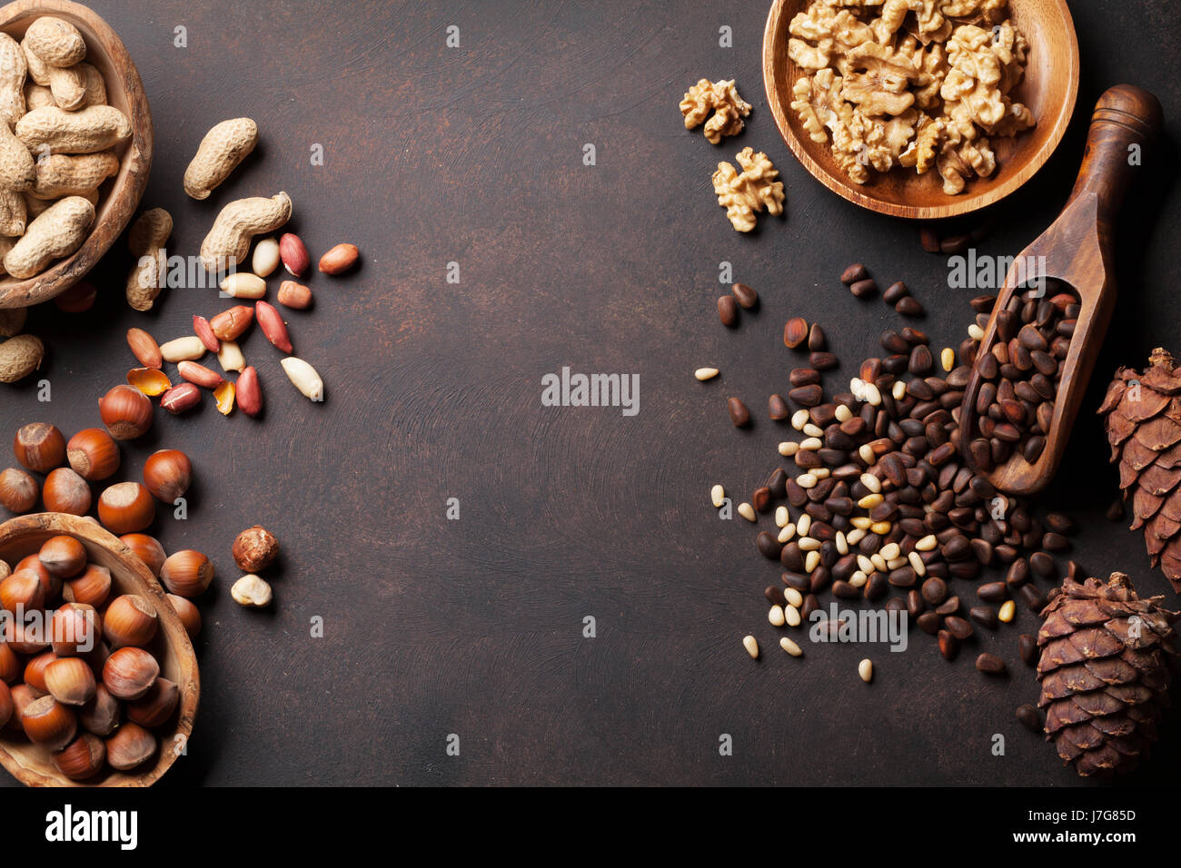 Various nuts on stone table. Top view with copy space - Stock Image