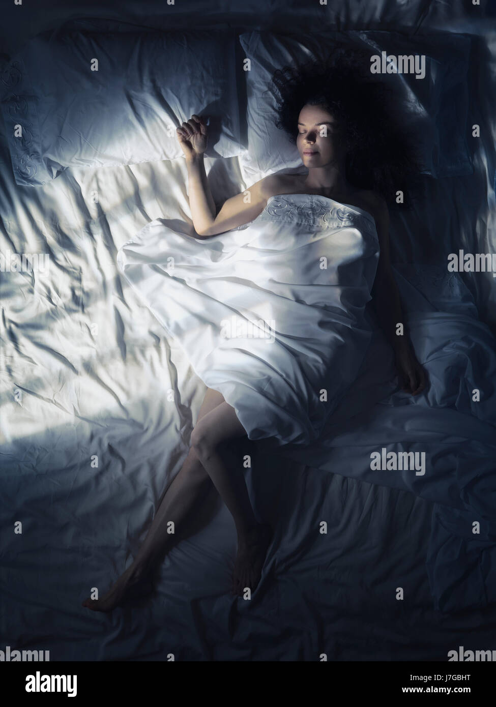 Young Woman Sleeping Alone In Bed At Night Dark Bedroom Lit By Moonlight