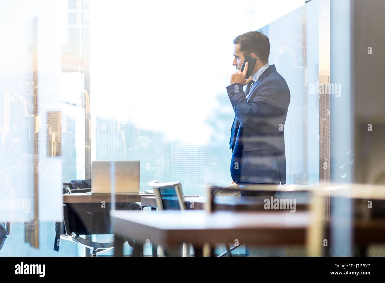 Businessman talking on a mobile phone while looking through window in NY - Stock Image