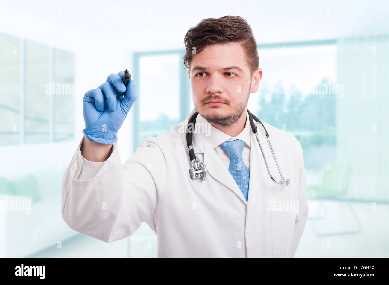 Confident doctor writing something in the air with marker on imaginary screen - Stock Image