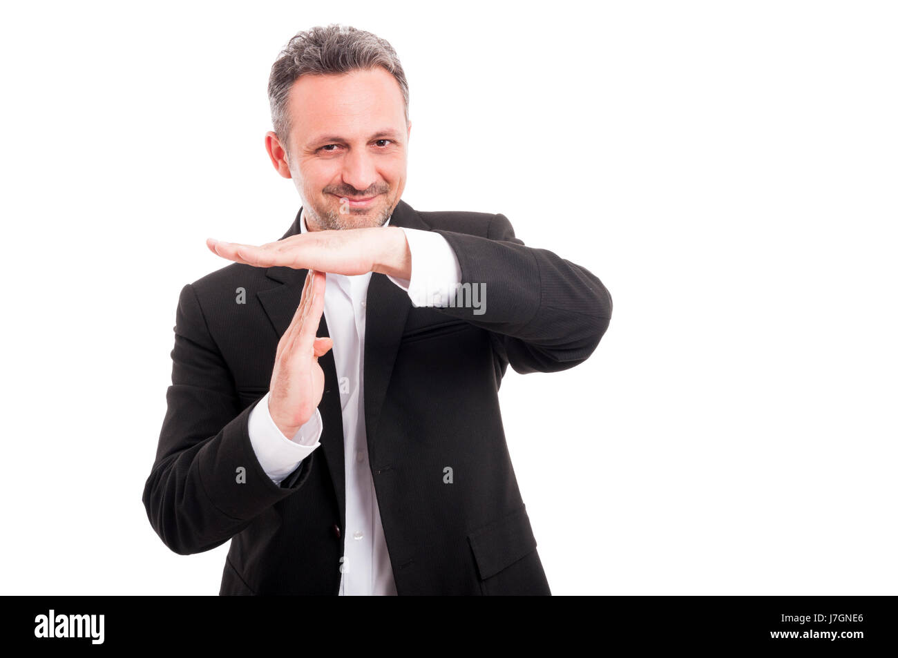 Handsome businessman showing time out or pause gesture and smiling on white studio background - Stock Image