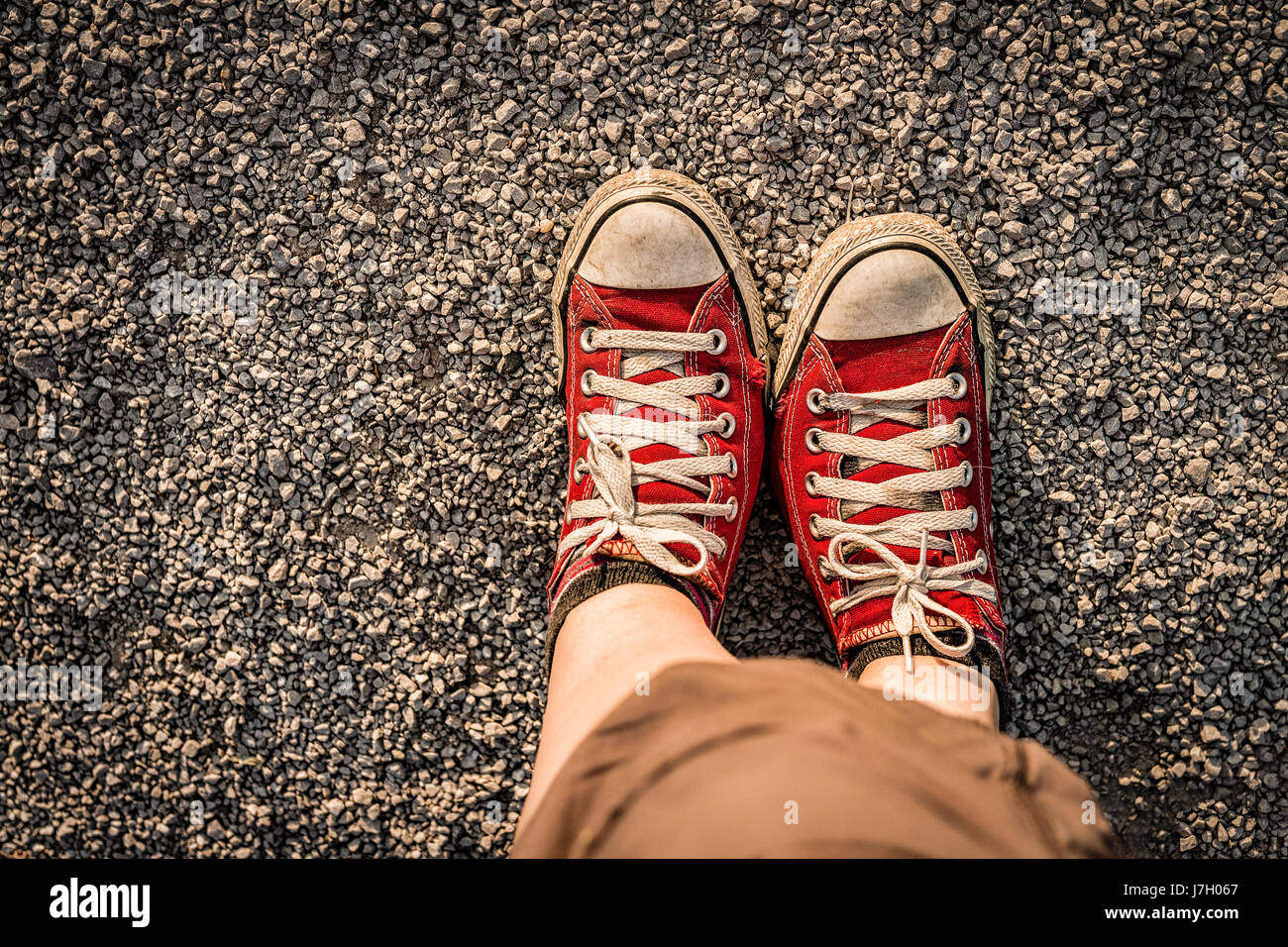 Feet in the red canvas sneakers on the gravel path - Stock Image