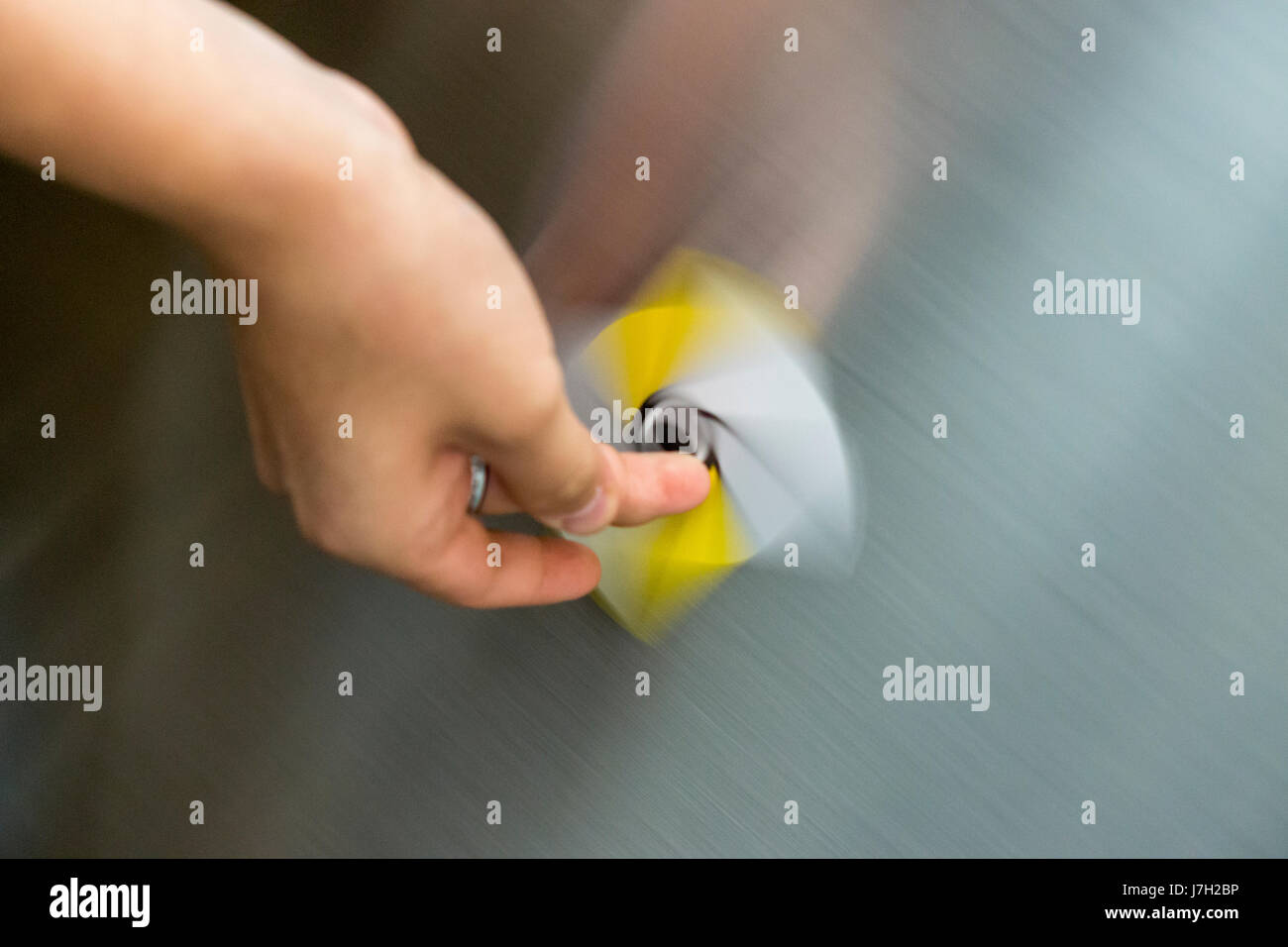 Card being spun on the side of an escalator Stock Photo