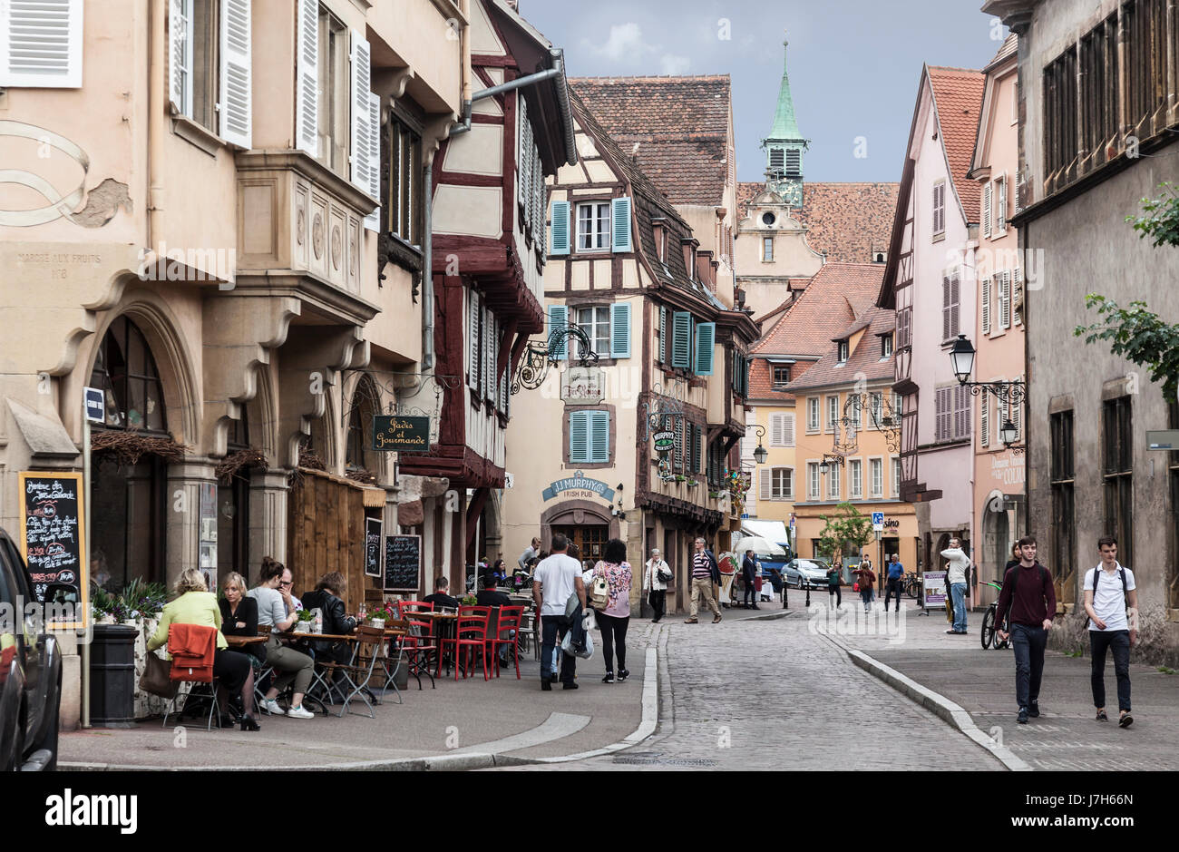 People walking in and sitting in pavement cafes in the medieval half-timbered buildings - now homes and businesses - Stock Image