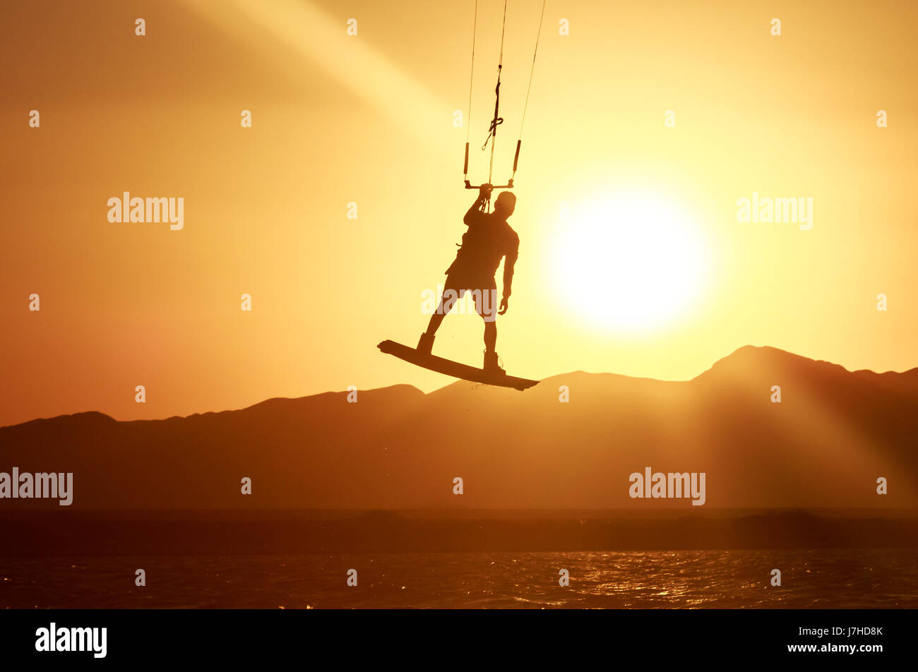 Kite boarder sportsman with kite under sunset sun, freestyle kiteboarding rider on the evening kite session, sunset - Stock Image