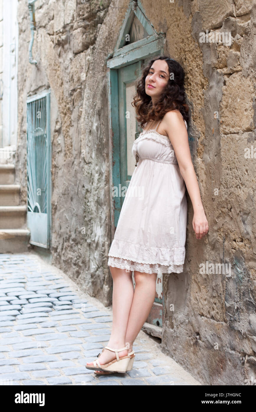 Young girl near old wall in downtown in Baku - Stock Image