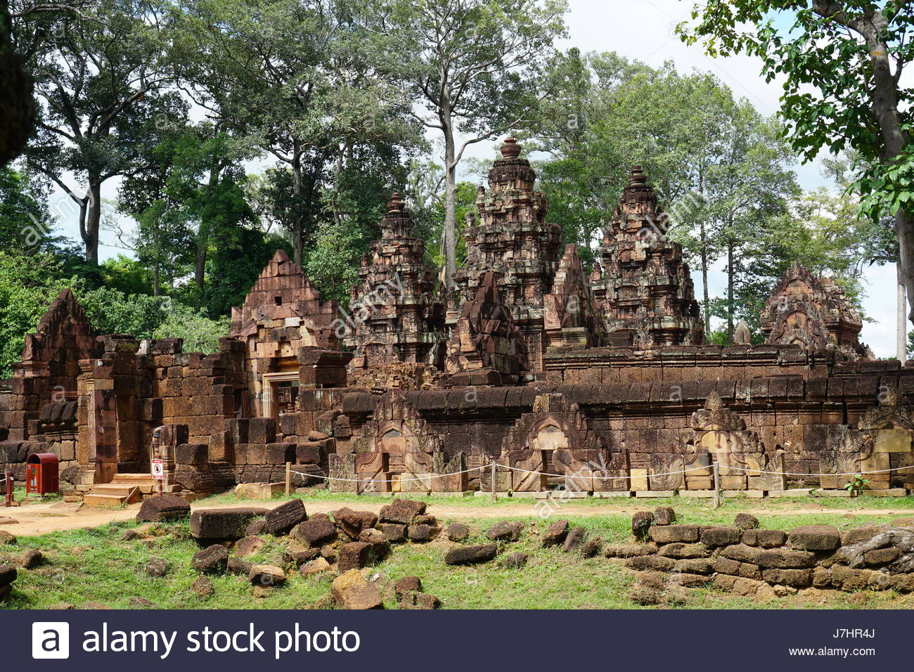 The mandapa and central tower, seen from the northeast. The intricate reliefs carving of red colored stone at Banteay - Stock Image