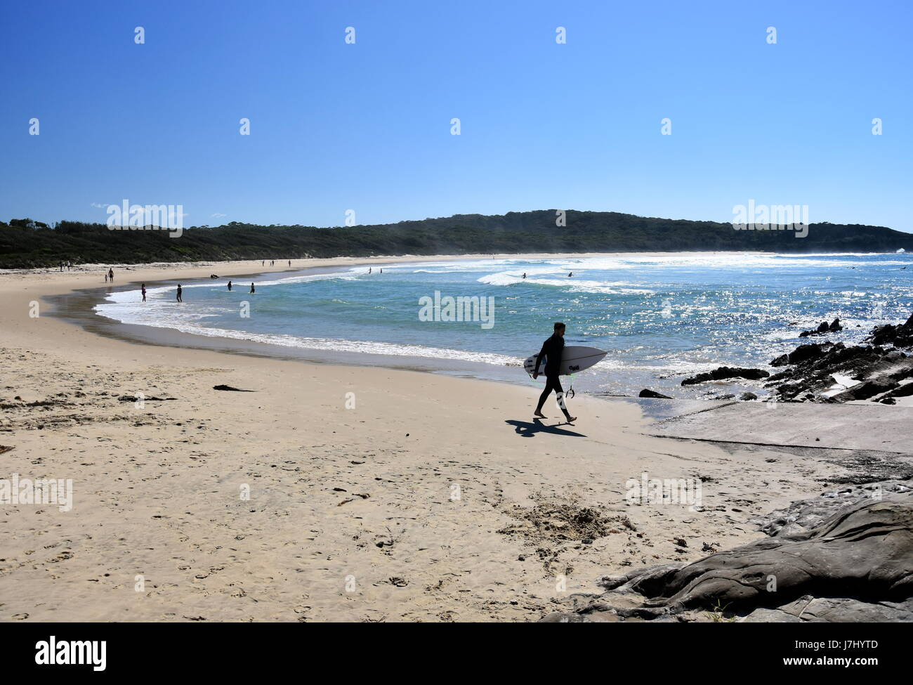 Potato Point, Australia - Apr 14, 2017. Men with surboard walking on the beach. Potato Point is a village in the - Stock Image