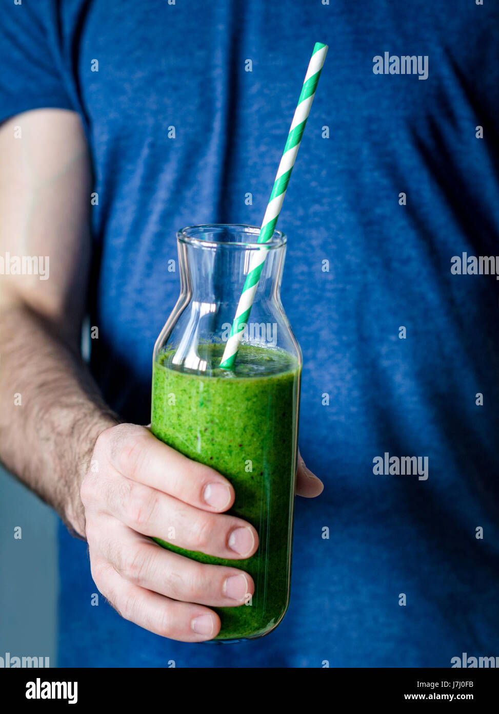 Green smoothie. Man hands holding bottle with freshly made detox green smoothie. Closeup view, selective focus Stock Photo