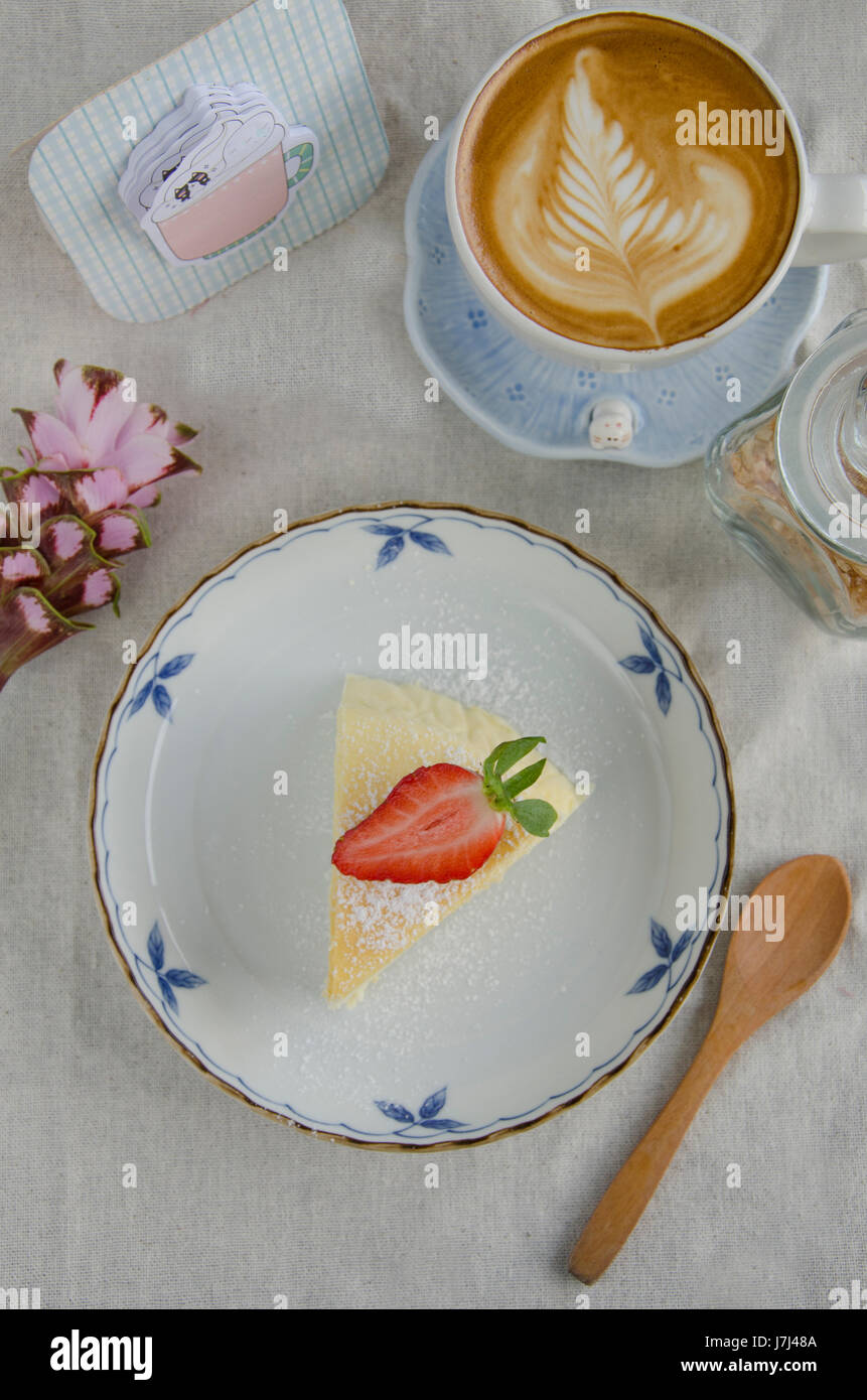 Cheese Cake On Top With Strawberry And Cup Of Latte Art On White