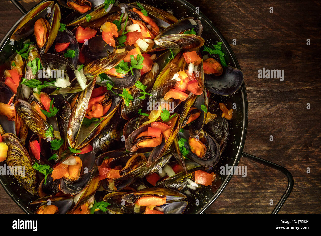 Skillet of marinara mussels on rustic background with copyspace - Stock Image