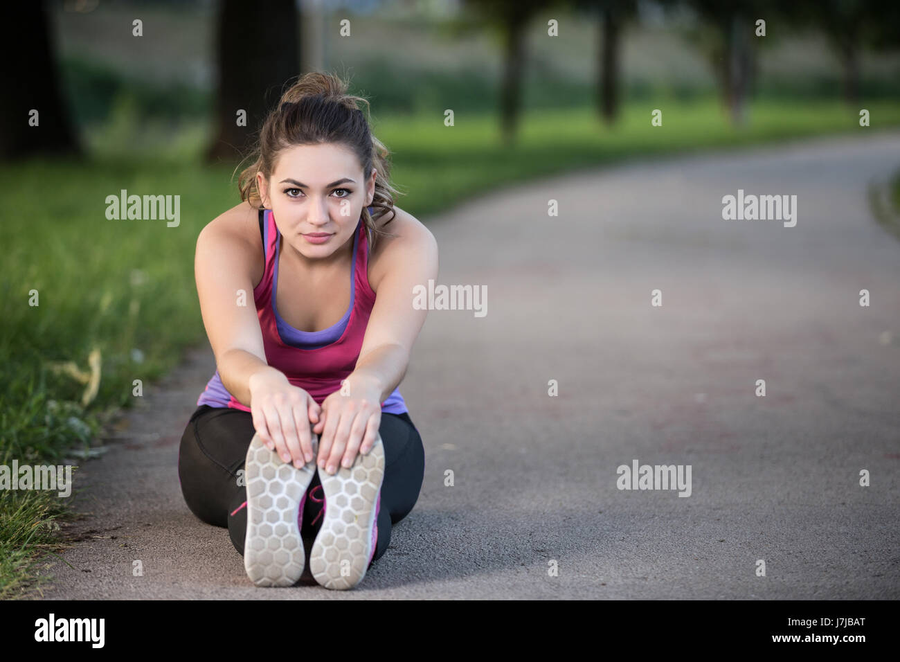 Woman is stretching before jogging. Fitness and lifestyle concept. - Stock Image