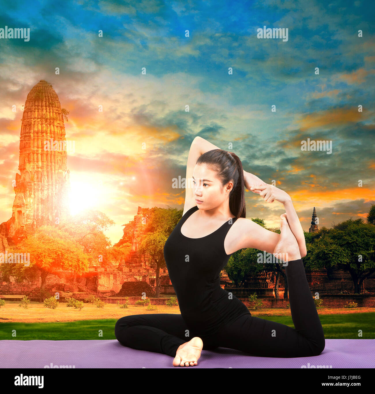 asian woman health care yoga posting with asian ancient pagoda temple and sun set sky - Stock Image