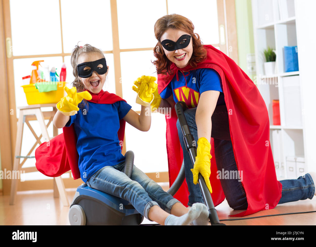 Kid girl and her mother weared Superhero costumes. Cute helper child and woman make cleaning room and have a fun. - Stock Image