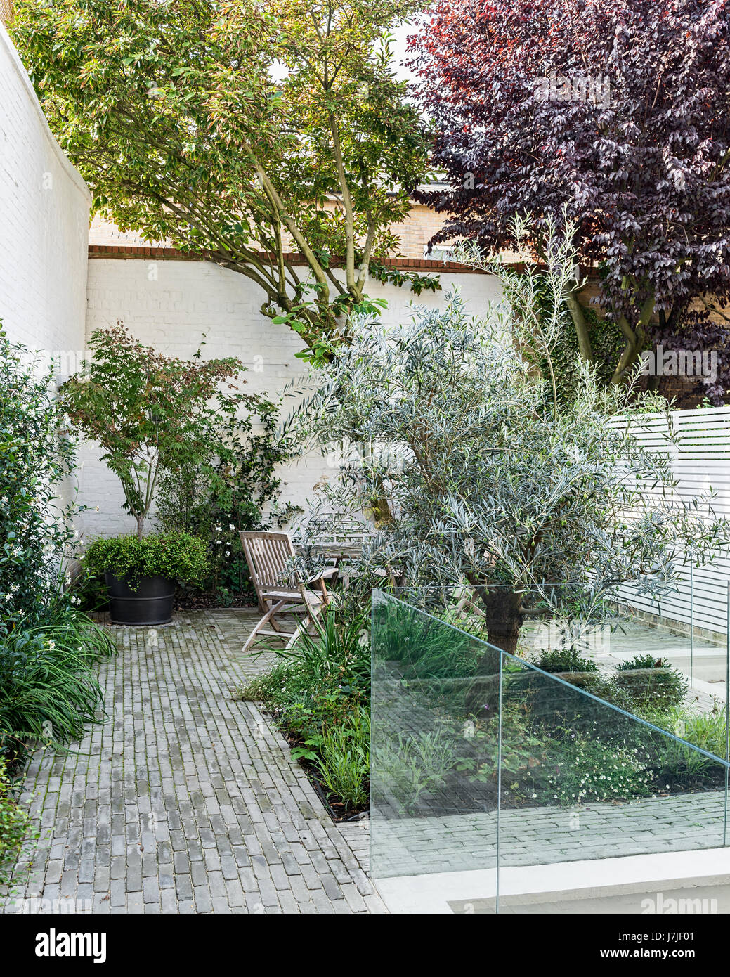 White Painted Walls And Pale Horizontal Wood Trellis In Garden With  Traditional Vande Moortel Pavers. Landscaping By Garden Makers.