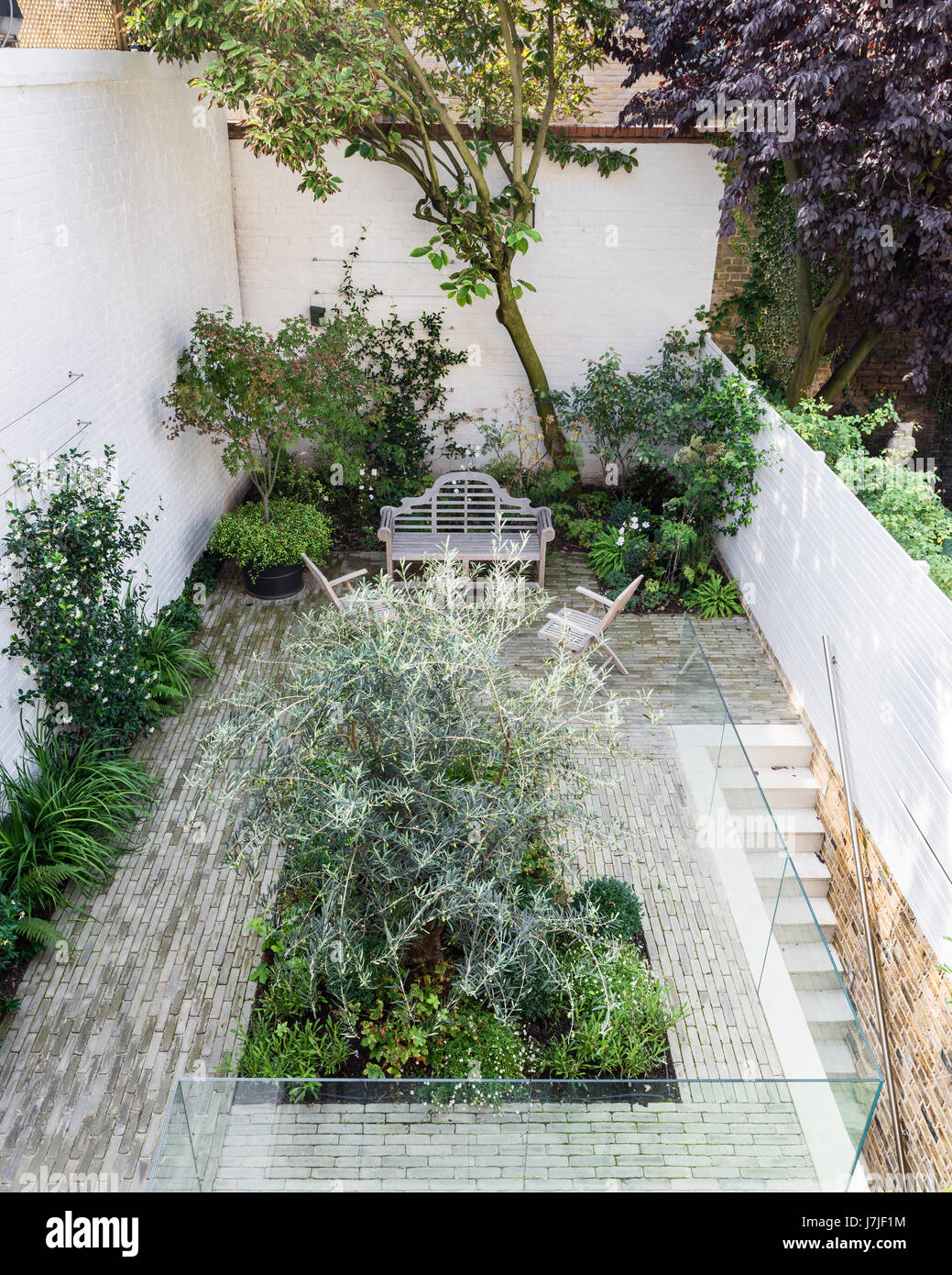 White Painted Walls And Pale Horizontal Wood Trellis In Garden Landscaped  By Garden Makers.