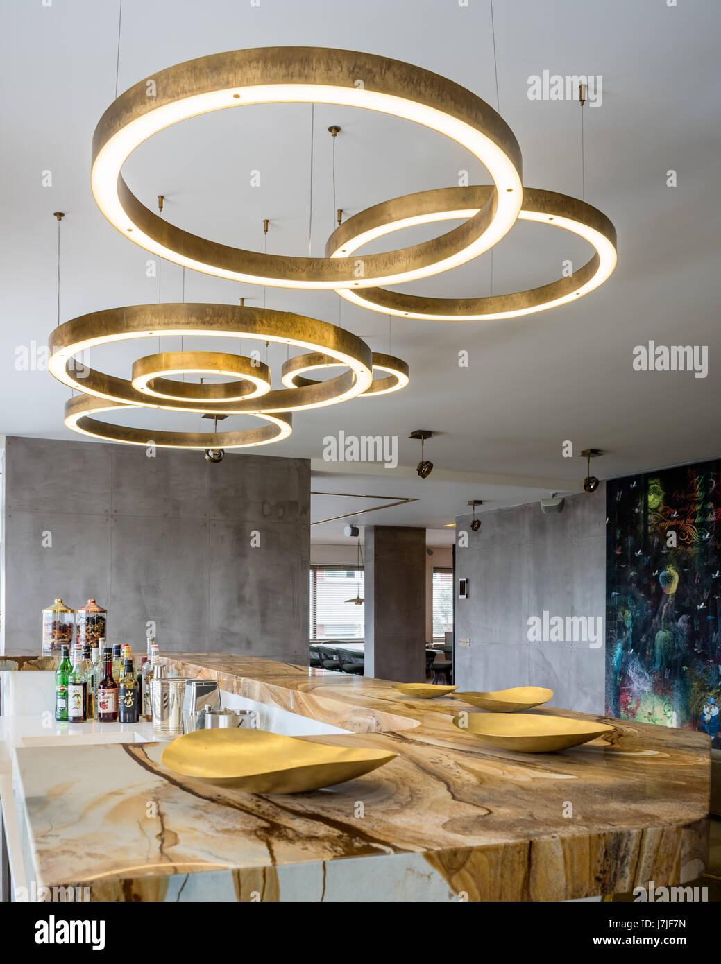 Circular brass light fittings above stonewood marble and onyx bar in Istanbul apartment - Stock Image