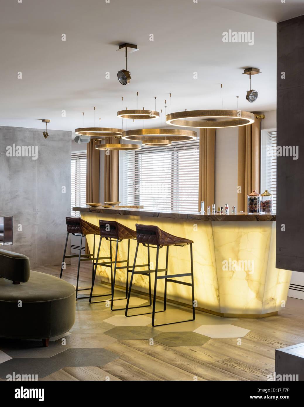 Circular lighting above lit bar area in Istanbul apartment - Stock Image