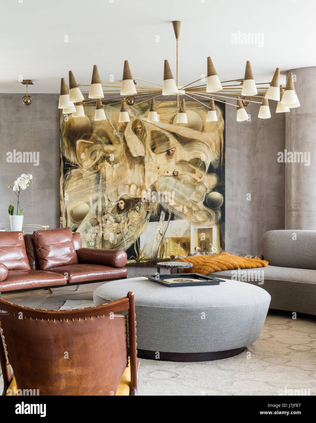 Large modern artwork with 1950s lighting above informal seating - Stock Image