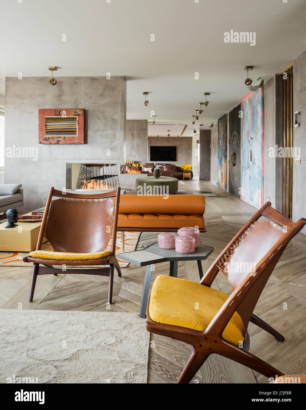 Pair of brown leather, vintage Saddler chairs in 30 meter open plan living space - Stock Image