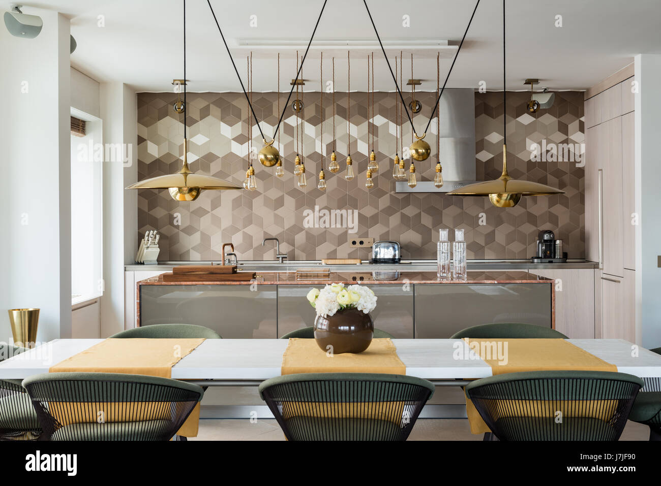 Marble worktop kitchen island with Bulthaup units and brass hanging lights - Stock Image