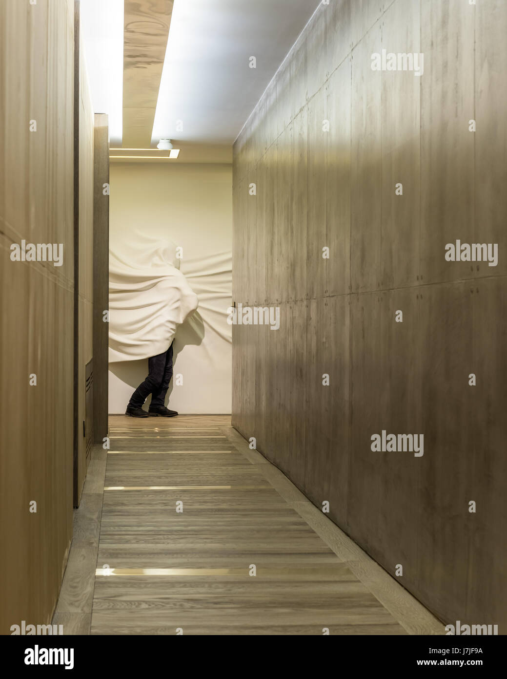 Shrouded figure sculpted from powdered glass by Daniel Arsham in hallway with polished concerete walls Stock Photo