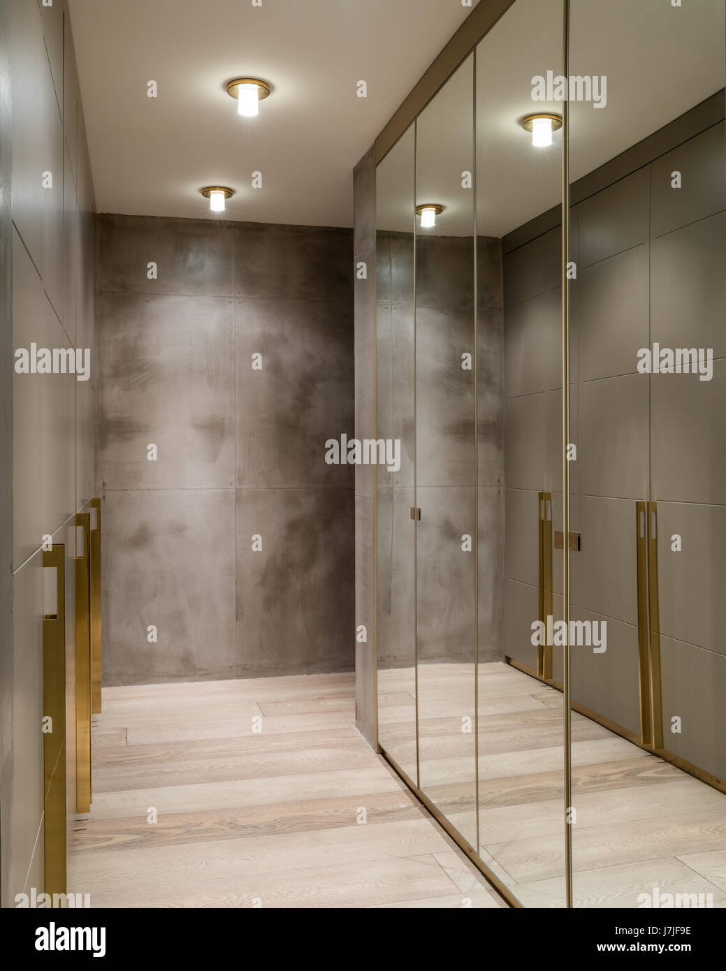 Mirrored Wardrobes In Dressing Room With Polished Concrete