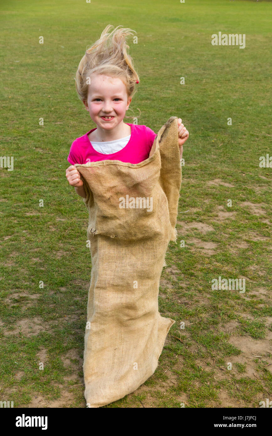 Seven-year-old girl / Child / kid takes part in summer sack race. UK (87) - Stock Image
