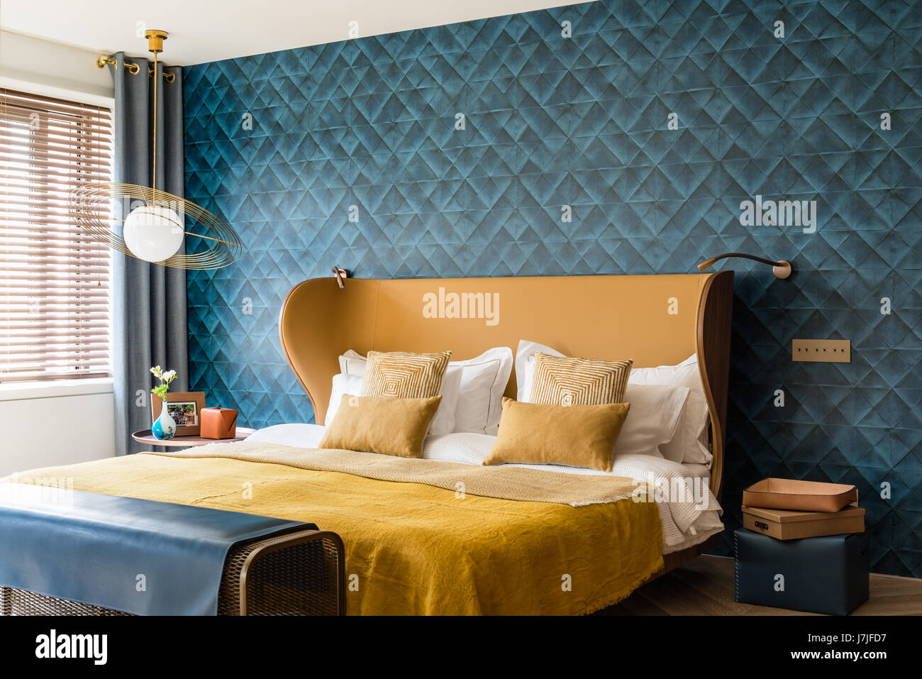 Saturno hanging light beside modernist style bed with vintage linen throws - Stock Image
