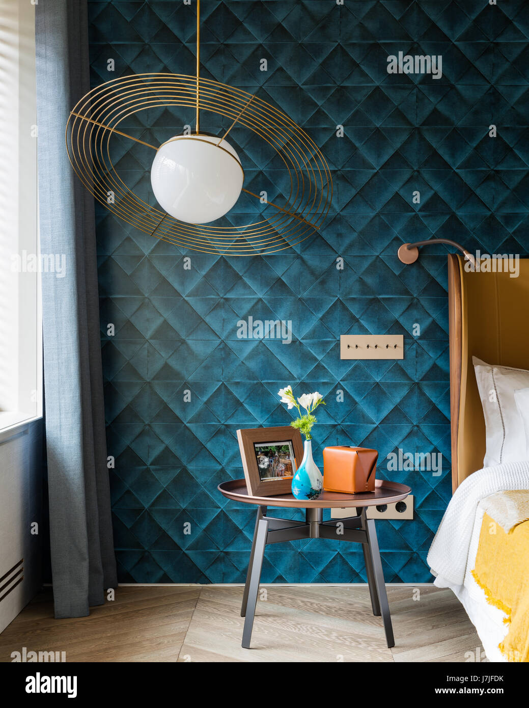 Saturno hanging light with blue quilted style wallpaper - Stock Image