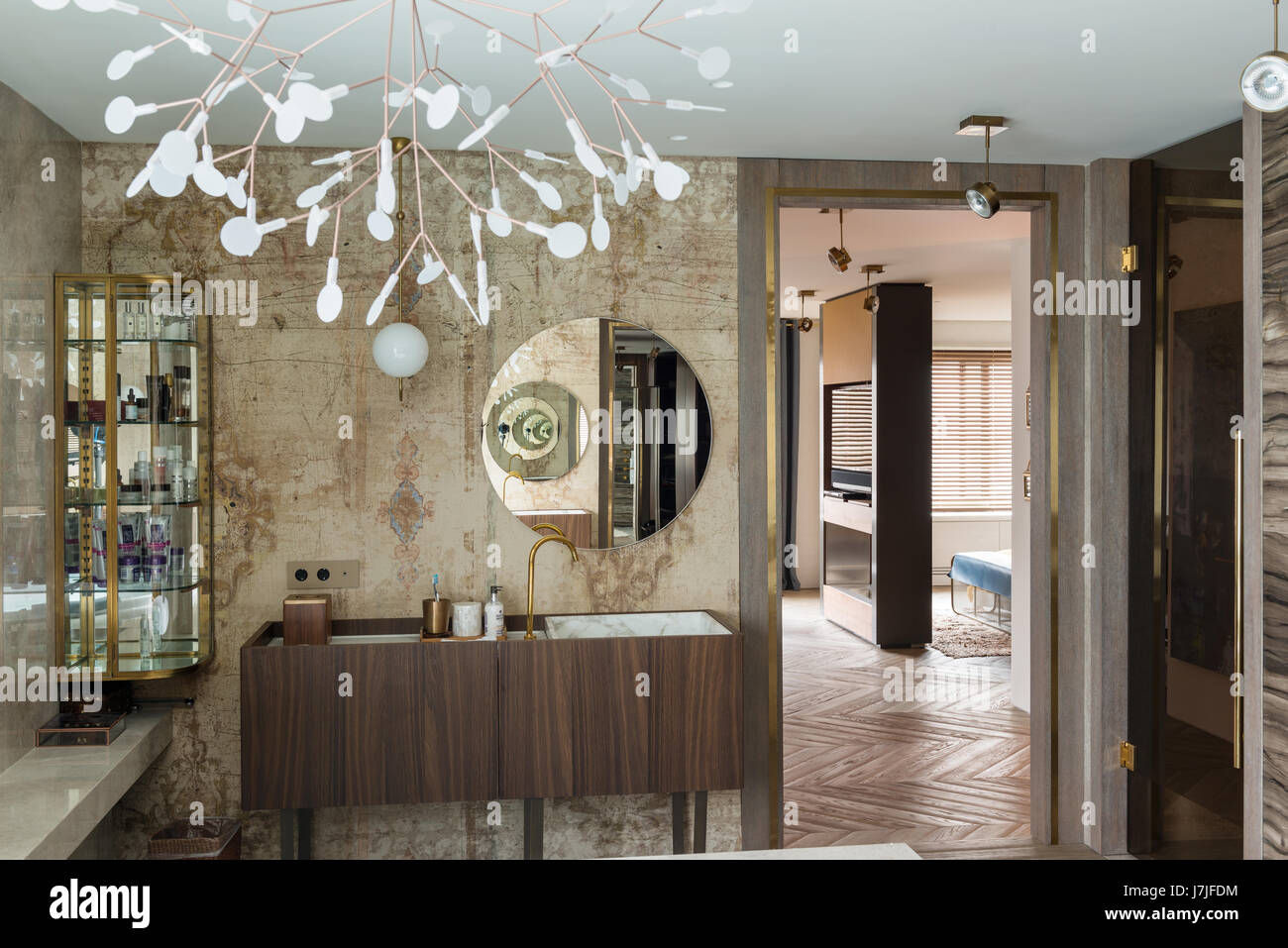 Circular mirror above washbasin with elaborate sculpture - Stock Image