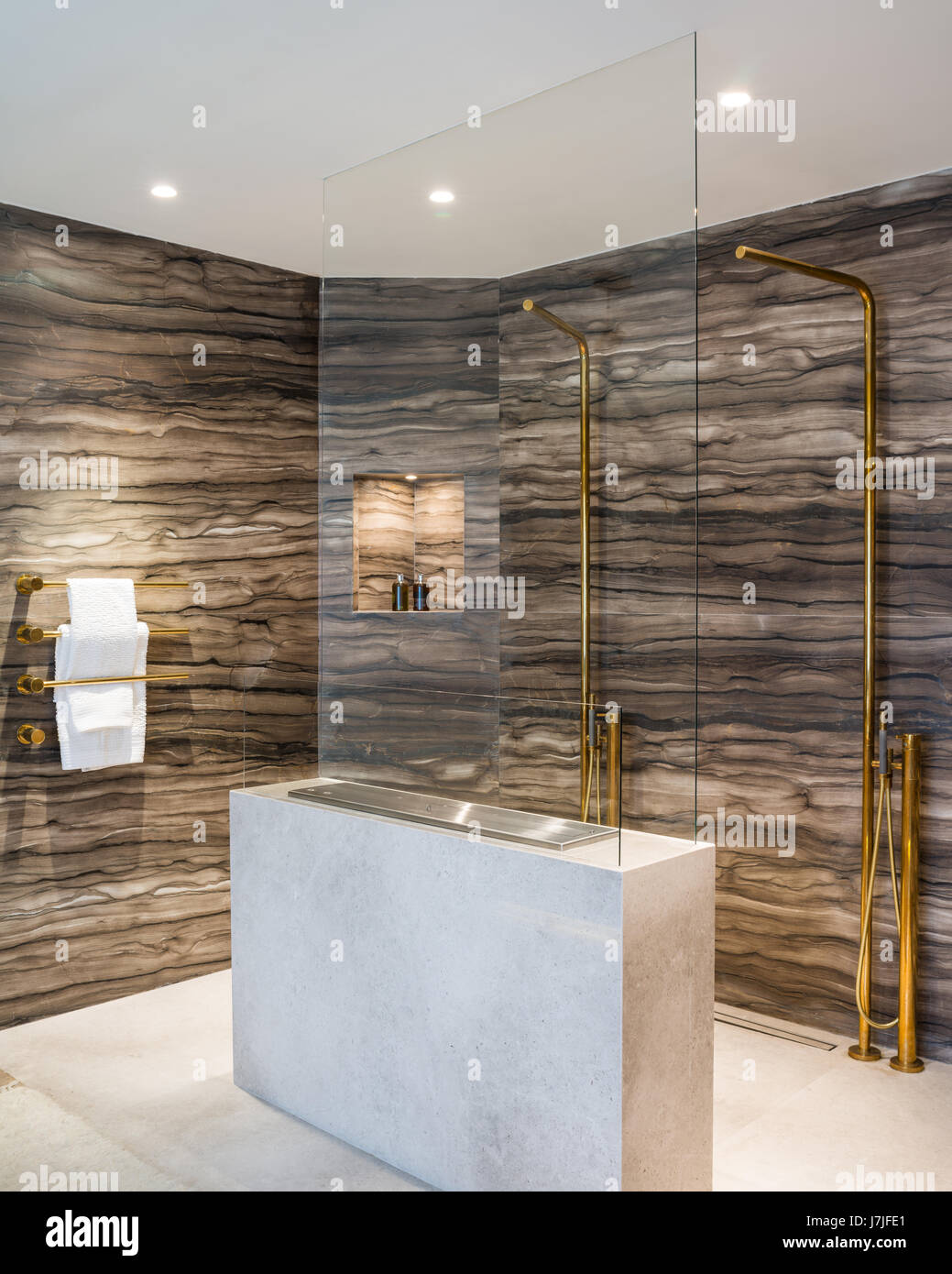 Sienna brown marble lines walls of shower area with gas fire - Stock Image