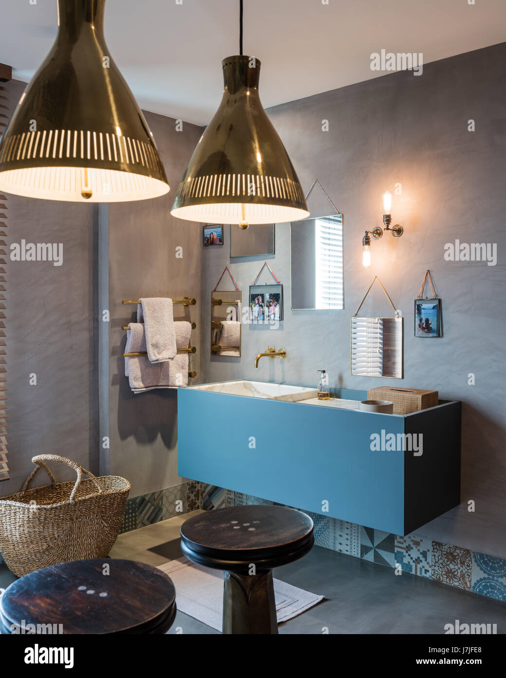 Pair of matching pendant lights in bathroom with assorted mirrors above washstand - Stock Image