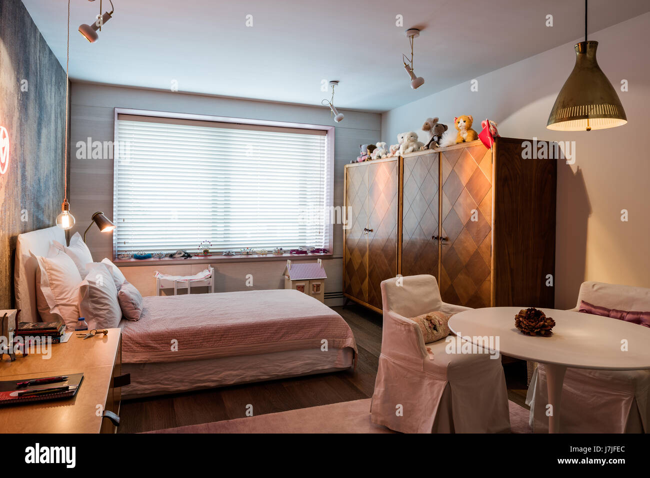 Soft toys on wardrobe in girl's room with closed Venetian blinds - Stock Image