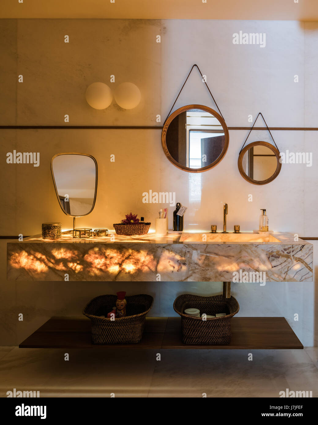 Wood framed mirrors above lit marble wash stand - Stock Image