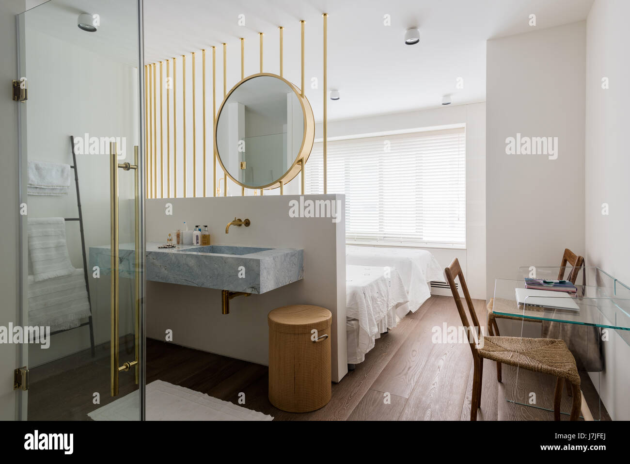 Large brass mirror above ensuite wash stand in twin bedroom - Stock Image