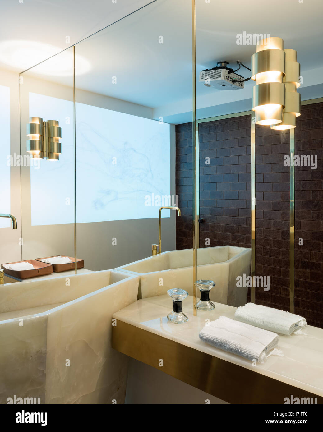 Brass fittings with full length mirror and reflection of marble washstand - Stock Image