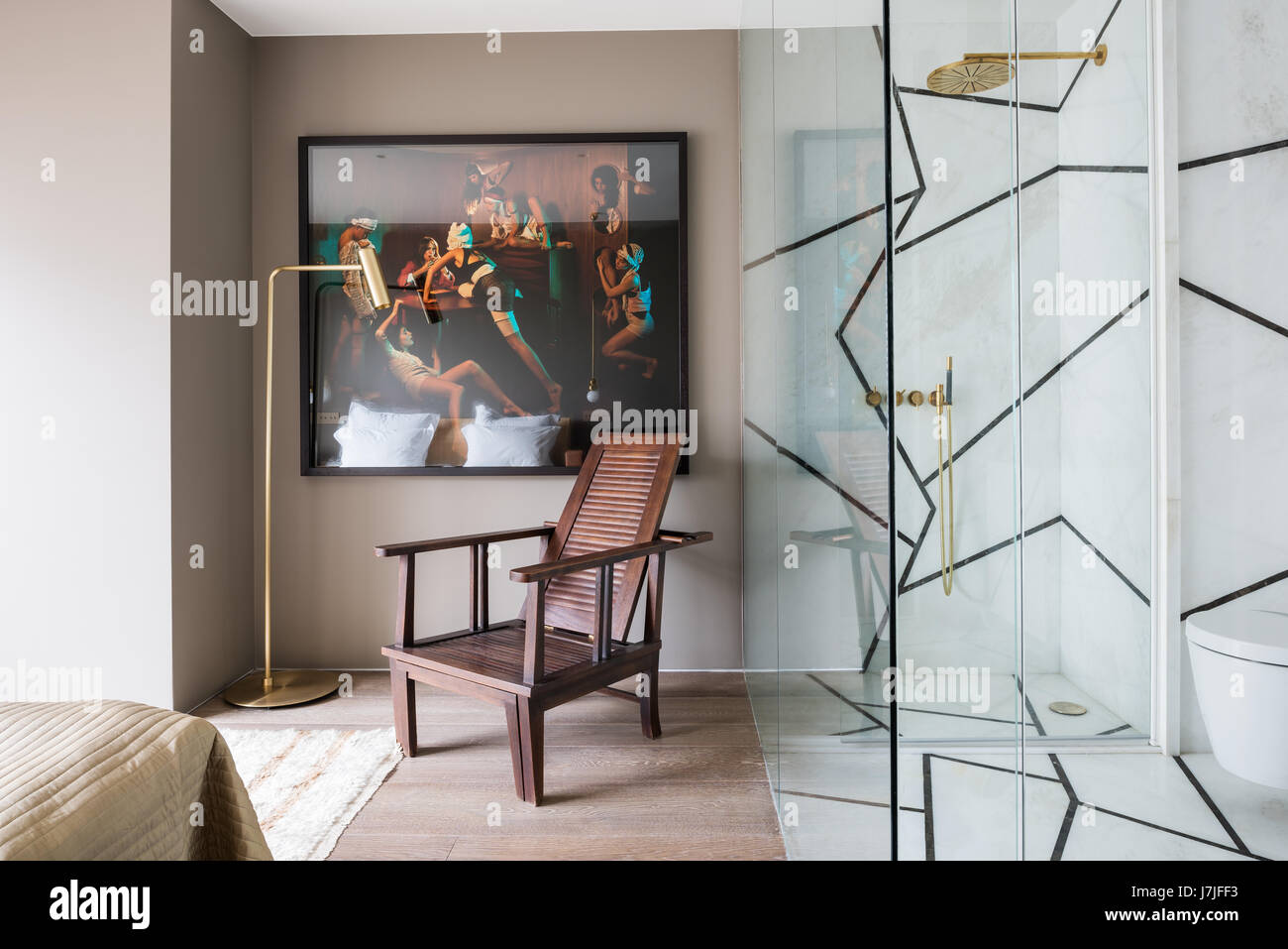 Wooden chair below painting by Olivier Masmonteil with glass screened ensuite - Stock Image