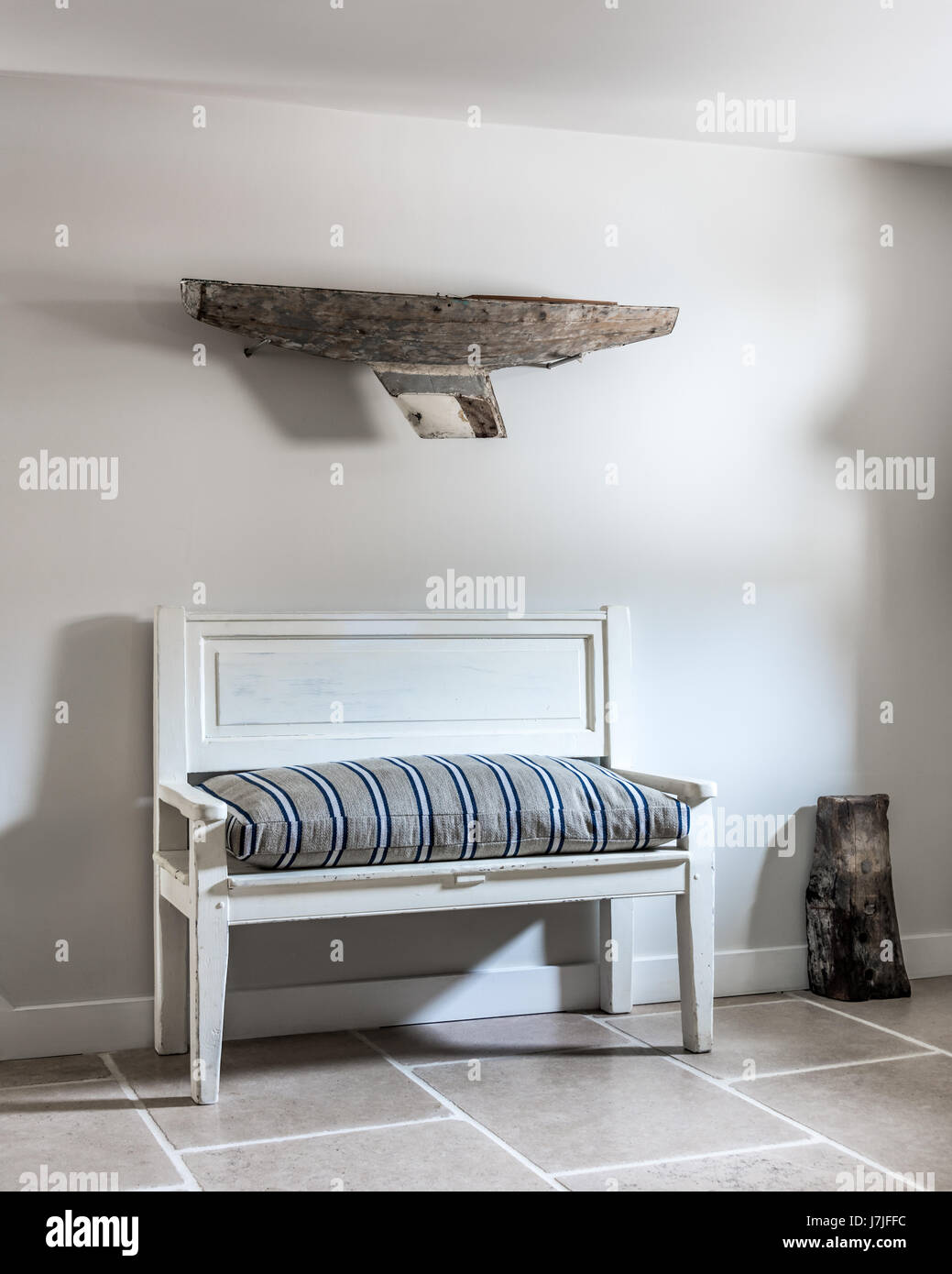 A driftwood boat on wall above antique bench with ticking stripe cushion. The walls are painted in Farrow & - Stock Image