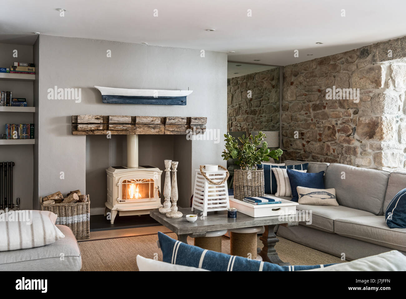Jotul Wood Stove In Sitting Room With Exposed Stone Wall And Mirrored  Alcove. A Driftwood Boat Hangs Above The Fireplace And The Walls Are  Painted In
