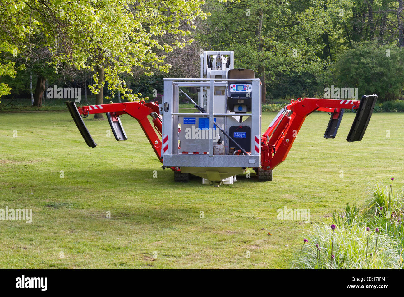 Self propelled cherry picker with extendable legs and caterpillar tracks being used to cut branches from trees - Stock Image