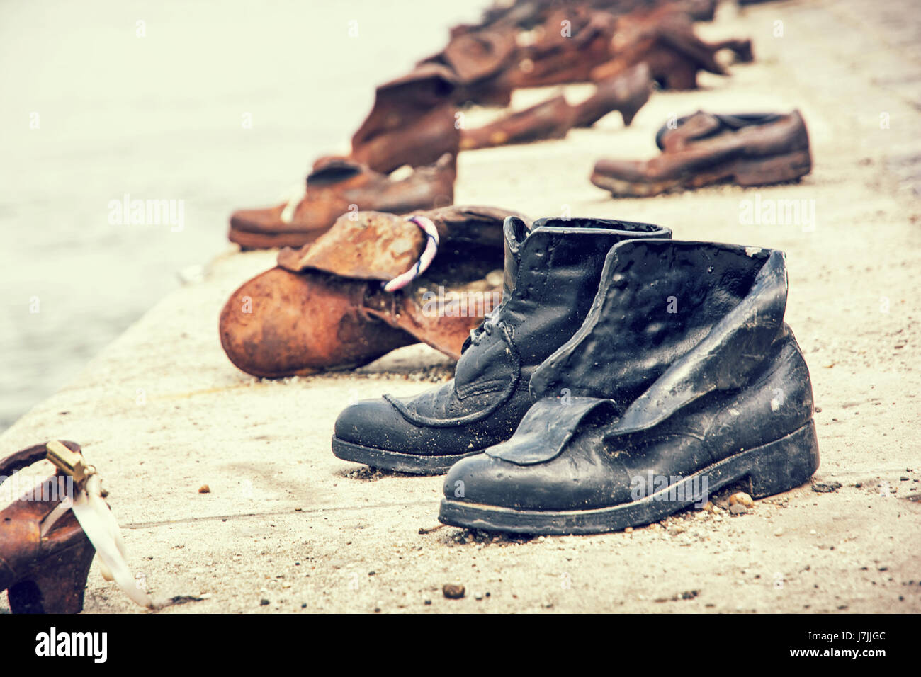 Shoes monument on the Danube bank is a memorial in Budapest, Hungary. Retro photo filter. Symbolic artistic object. - Stock Image